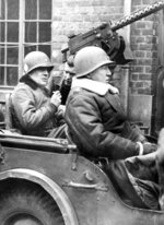 "FILE - In this Jan. 15, 1945 file photo, U.S. Brig. Gen. Anthony C. McAuliffe, left, and Lt. Gen. George S. Patton, Jr., right, are seated in Jeep after made an inspection tour of the 101st Airborne division. At first, German forces drove so deep through the front line in Belgium and Luxembourg that the month-long fighting came to be known as The Battle of the Bulge. When the Germans asked one American commander to surrender, the famous reply came: ""Nuts!"