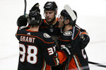Anaheim Ducks right wing Carter Rowney, right, celebrates his empty-net goal with center Derek Grant, left, and center Ryan Getzlaf, center, during the third period of the team's NHL hockey game against the Winnipeg Jets in Anaheim, Calif., Tuesday, Oct. 29, 2019. Rowney scored twice in the third period as the Ducks won 7-4. (AP Photo/Alex Gallardo)