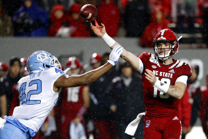 North Carolina State quarterback Devin Leary (13) is hurried on a throw by North Carolina's Tyrone Hopper (42) during the first half of an NCAA college football game in Raleigh, N.C., Saturday, Nov. 30, 2019. (AP Photo/Karl B DeBlaker)