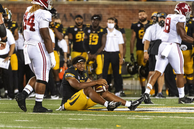 Missouri quarterback Shawn Robinson sits on the turf after he had his helmet knocked off while being sacked during the second half of an NCAA college football game against Alabama, Saturday, Sept. 26, 2020, in Columbia, Mo. (AP Photo/L.G. Patterson)