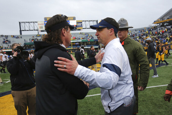 West Virginia head coach Neal Brown, right, shakes hands with Oklahoma State head coach Mike Gundy after an NCAA college football game in Morgantown, W.Va., on Saturday, Nov. 23, 2019. (AP Photo/Chris Jackson)