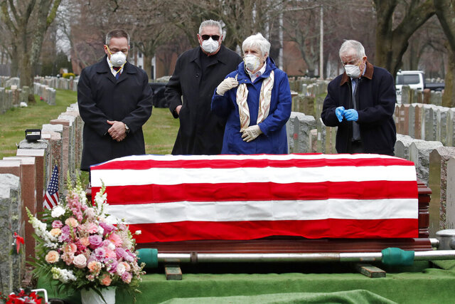 Mourners stand by the casket of veteran Mary Foley, Wednesday, April 8, 2020, in Malden, Mass. Foley, who died at the age of 93, served in the U.S. Air Force, including WWII. Due to the coronavirus crisis, she cannot be given a formal military funeral. (AP Photo/Elise Amendola)