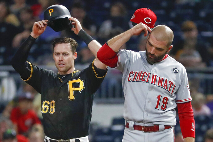 Pittsburgh Pirates' Jake Elmore (68) and Cincinnati Reds' Joey Votto (19) adjust their hats at the same time between pitches after Ellmore walked in the seventh inning of a baseball game, Saturday, Sept. 28, 2019, in Pittsburgh. (AP Photo/Keith Srakocic)