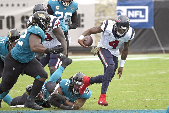 Houston Texans quarterback Deshaun Watson (4) scrambles away from Jacksonville Jaguars defensive end Dawuane Smoot (94), defensive tackle DaVon Hamilton, left, and safety Jarrod Wilson (26) during the second half of an NFL football game, Sunday, Nov. 8, 2020, in Jacksonville, Fla. (AP Photo/Phelan M. Ebenhack)