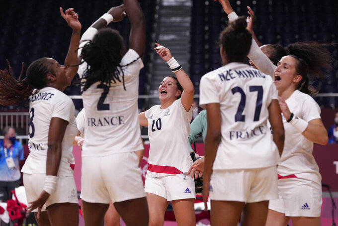 France's team players celebrate as they won the women's gold medal handball match between the Russian Olympic Committee and France at the 2020 Summer Olympics, Sunday, Aug. 8, 2021, in Tokyo, Japan. (AP Photo/Pavel Golovkin)
