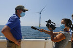 Virginia Gov. Ralph Northam, left, is interviewed by a reporter as he looks over one of two offshore wind turbines off the coast of Virginia Beach, Va., Monday, June 29, 2020. Two wind turbines have been constructed 20 miles off the coast of Virginia Beach as part of an offshore wind turbine project. The turbines will begin operation in August. (AP Photo/Steve Helber)