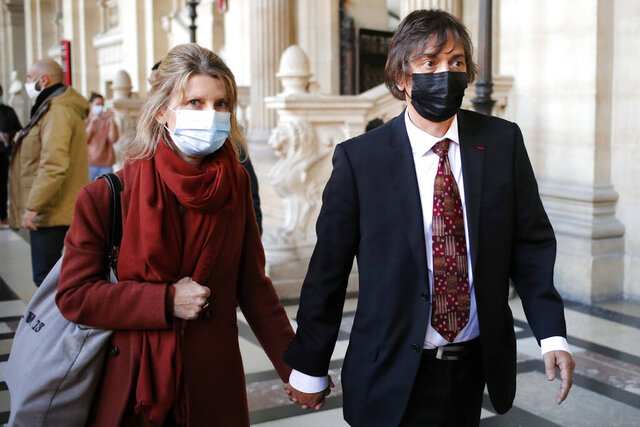French-American Mark Moogalian, right, and his wife Isabelle arrive at the Thalys attack trial, at the Paris courthouse, Thursday, Nov. 19, 2020. The lawyer for an American who was scheduled to testify about his role in the dramatic capture of an Islamic State operative aboard a high-speed train says his witness has been hospitalized after he flew in to Paris. (AP Photo/Francois Mori)