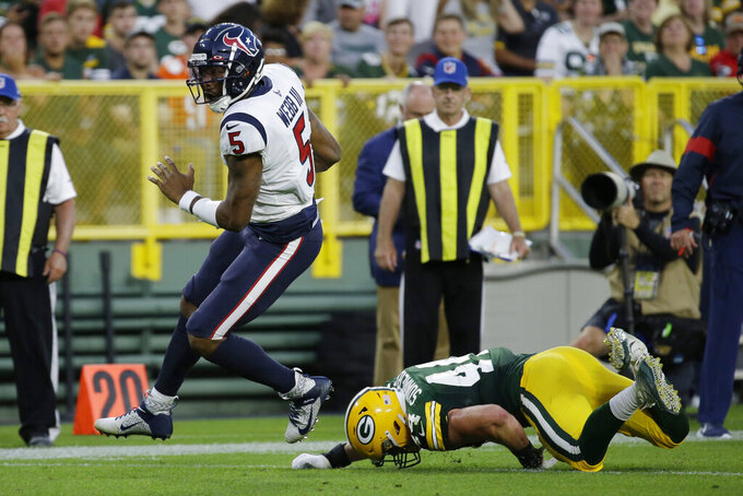 Houston Texans quarterback Joe Webb rushes, breaking the tackle of Green Bay Packers linebacker Ty Summers during the first half of an NFL preseason football game Thursday, Aug. 8, 2019, in Green Bay, Wis. (AP Photo/Mike Roemer)