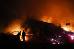 FILE - In this Dec. 7, 2017, file photo, two firefighters watch as a home burns in a wildfire in La Conchita, Calif. Attorneys say as many as 100,000 Californians are eligible to receive payments for the damages they've suffered from a series of devastating wildfires over the last several years, but tens of thousands of them have not. They face a Monday, Oct. 21, 2019, deadline to file claims against Pacific Gas & Electric, the utility blamed for many of the fires. (AP Photo/Jae C. Hong, File)