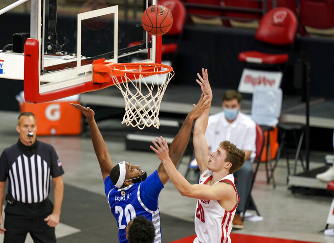 Wisconsin's Ben Carlson, right, shoots over Eastern Illinois' Sammy Friday (20) during the first half of an NCAA college basketball game Wednesday, Nov. 25, 2020, in Madison, Wis. (AP Photo/Andy Manis)