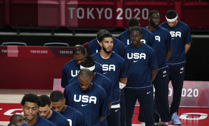 United States players stand during their national anthem prior to men's basketball preliminary round game between United States and Iran at the 2020 Summer Olympics, Wednesday, July 28, 2021, in Saitama, Japan. (AP Photo/Eric Gay)