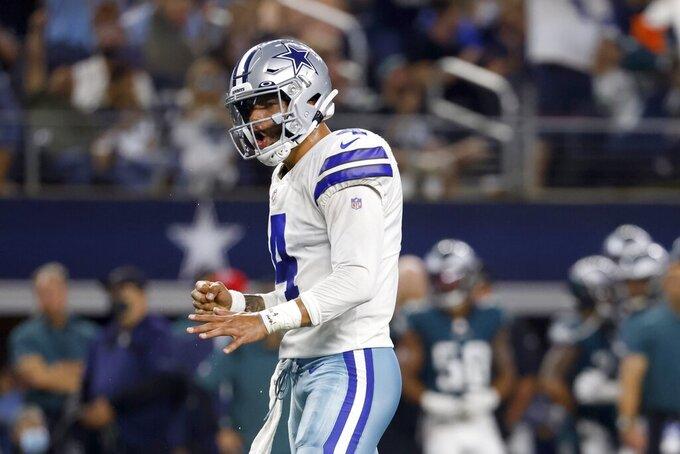 Dallas Cowboys quarterback Dak Prescott (4) celebrates after a touchdown run by running back Ezekiel Elliott in the first half of an NFL football game against the Philadelphia Eagles in Arlington, Texas, Monday, Sept. 27, 2021. (AP Photo/Ron Jenkins)