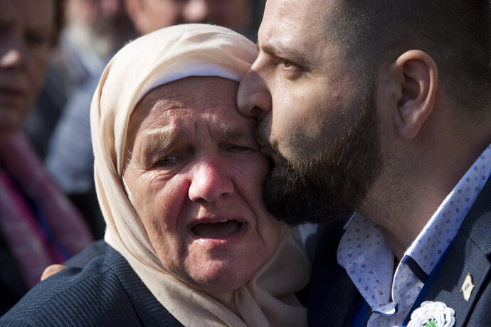 A crying woman with the Mothers of Srebrenica is hugged after the court upheld the convictions of former Bosnian Serb leader Radovan Karadzic at International Residual Mechanism for Criminal Tribunals in The Hague, Netherlands, Wednesday, March 20, 2019. Nearly a quarter of a century since Bosnia's devastating war ended, Karadzic heard the final judgment upholding 2016 convictions for genocide, crimes against humanity and war crimes, and increased his 40-year sentence to life. (AP Photo/Peter Dejongl)