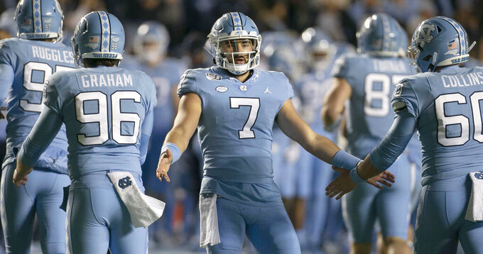 North Carolina quarterback Sam Howell (7) congratulates teammates after the Tar Heels scored against Virginia in the second quarter of an NCAA college football game Saturday, Nov. 2, 2019, in Chapel Hill, N.C. (Robert Willett/The News & Observer via AP)