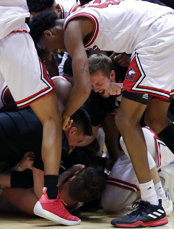 Northern Illinois forward Noah McCarty, bottom, celebrates with teammates after scoring the game-winning basket against Buffalo during the second half of an NCAA college basketball game Tuesday, Jan. 22, 2019, in DeKalb, Ill. Northern Illinois won 77-75. (AP Photo/Nam Y. Huh)