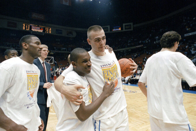 FILE - In this March 28, 1993, file photo, North Carolina's Donald Williams, center left, celebrates with teammate Eric Montross, center right, after Williams hit two three-point baskets in overtime to help North Carolina defeat Cincinnati 75-68 in an NCAA East Regional championship game at the Meadowlands Arena in East Rutherford, N.J. The player on the left is unidentified. Williams scored 25 points each in North Carolina's semifinal victory over Kansas and its championship game triumph over Michigan. (AP Photo/Bill Kostroun, File)