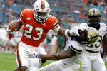 Miami running back Cam'Ron Davis (23) runs past Pittsburgh defensive back Damar Hamlin, right, during the first half of an NCAA college football game, Saturday, Nov. 24, 2018, in Miami Gardens, Fla. (AP Photo/Lynne Sladky)