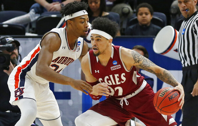 Auburn's forward Anfernee McLemore, left, guards New Mexico State forward Eli Chuha, right, in the first half during a first round men's college basketball game in the NCAA Tournament, Thursday, March 21, 2019, in Salt Lake City. (AP Photo/Rick Bowmer)