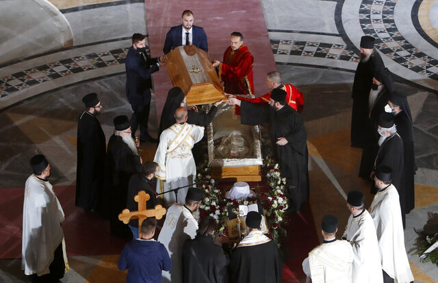 In this photo taken Saturday, Nov. 21, 2020, church leaders open the coffin of Patriarch Irinej during the procession at the St. Sava Temple in Belgrade, Serbia. After the two most senior Serbian Orthodox Church leaders died within a month after testing positive with the coronavirus, health experts and even hardcore believers are starting to worry. The spread of the virus within the largest religious group in the Balkans is getting more alarming by the day. (AP Photo/Darko Vojinovic)