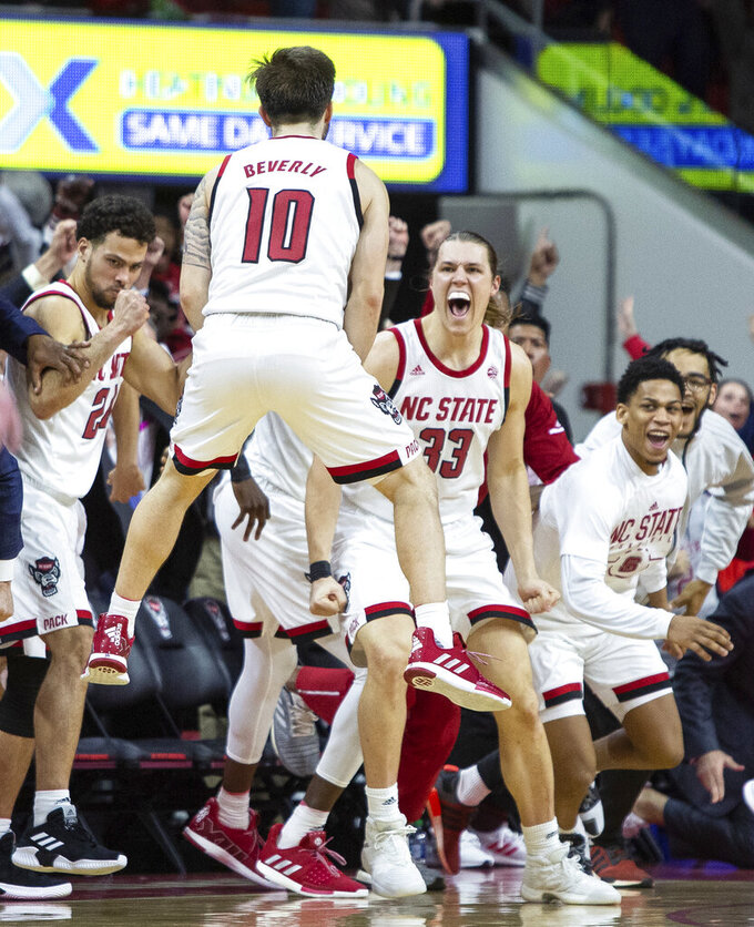 North Carolina State's Braxton Beverly (10) celebrates with teammates after hitting the game-winning 3-pointer in an NCAA college basketball game against Clemson in Raleigh, N.C., Saturday, Jan. 26, 2019. NC State won 69-67. (AP Photo/Ben McKeown)