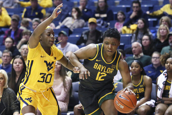 Baylor guard Moon Ursin (12) is defended by West Virginia guard Madisen Smith (30) during the second half of an NCAA college basketball game Monday, Feb. 24, 2020, in Morgantown, W.Va. (AP Photo/Kathleen Batten)