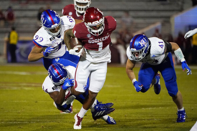 Oklahoma running back Seth McGowan (1) runs from Kansas defenders Nate Betts (34), Malcolm Lee (99) and Nick Channel (41) in the second half of an NCAA college football game in Norman, Okla., Saturday, Nov. 7, 2020. (AP Photo/Sue Ogrocki)