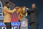 Calvin Johnson, a member of the Pro Football Hall of Fame Class of 2021, left, unveils his bust with his presenter Derrick Moore during the induction ceremony at the Pro Football Hall of Fame, Sunday, Aug. 8, 2021, in Canton, Ohio. (AP Photo/David Richard)