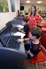In this May 8, 2019, photograph, Sharon Stidham, standing, talks to her sons Graham, center, and Miles, front, as they use the laptops at East Webster High School to do homework in Maben, Miss. A cellphone tower is visible through the trees from their home on a hilltop near Maben, but the internet signal does not reach their house, despite building a special antenna on top of a nearby family cabin. (AP Photo/Rogelio V. Solis)