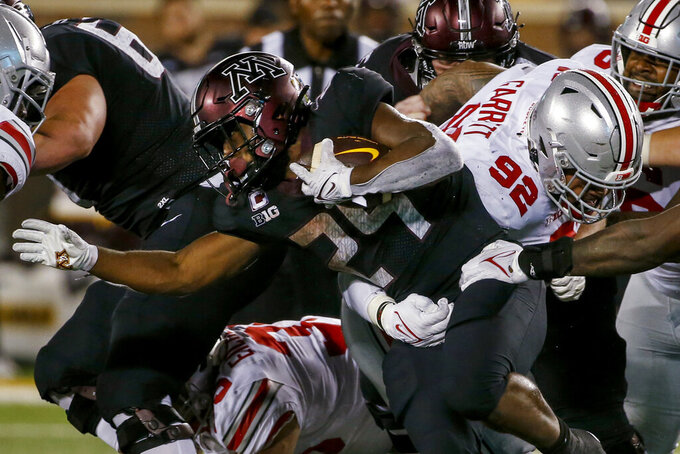 Minnesota running back Mohamed Ibrahim (24) rushes past Ohio State linebacker Haskell Garrett (92) during the second half of an NCAA college football game Thursday, Sept. 2, 2021, in Minneapolis. Ohio State won 45-31. (AP Photo/Bruce Kluckhohn)