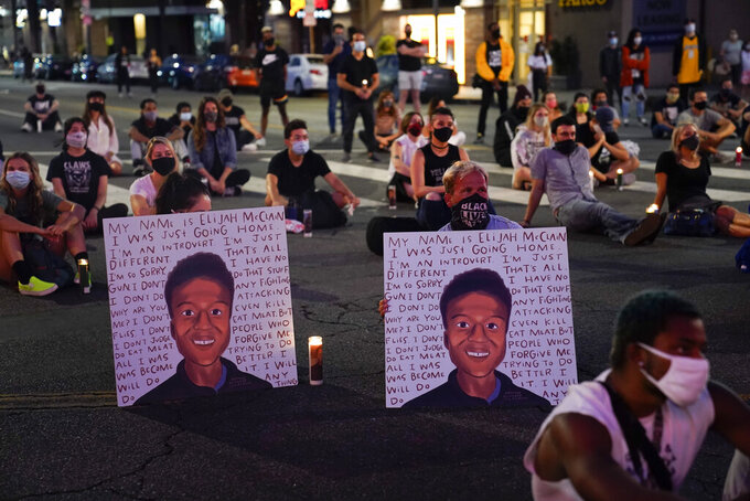 FILE - In this Aug. 24, 2020, file photo, two people hold posters showing images depicting Elijah McClain during a candlelight vigil for McClain outside the Laugh Factory in Los Angeles. Colorado police reform advocates say the recent indictments of three suburban Denver police officers and two paramedics on manslaughter and other charges in the death of Elijah McClain could be a pivotal step toward meaningful accountability. (AP Photo/Jae C. Hong, File)