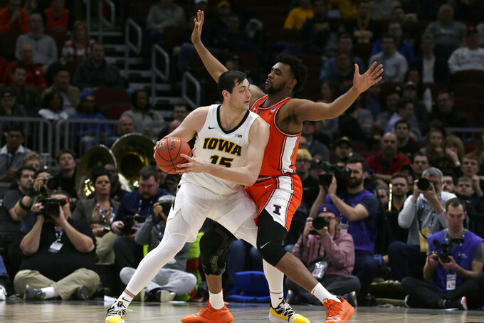 Iowa's Ryan Kriener (15) looks to pass against Illinois's Adonis De La Rosa during the second half of an NCAA college basketball game in the second round of the Big Ten Conference tournament, Thursday, March 14, 2019, in Chicago. (AP Photo/Kiichiro Sato)
