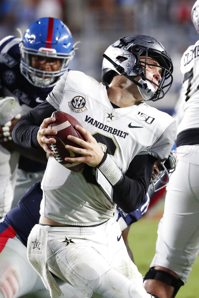 Vanderbilt quarterback Riley Neal (6) spins away from a Mississippi defender during the second half of an NCAA college football game in Oxford, Miss., Saturday, Oct. 5, 2019. (AP Photo/Rogelio V. Solis)
