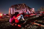 In this Sunday, Oct. 20, 2019 photo, Henry Ramirez, a member of Primera Iglesia Dallas, is consoled by his mother Maribel Morales as they survey severe damage to the church, where Ramirez plays drums and Morales attends, after a tornado tore through North Dallas. (AP Photo/Jeffrey McWhorter)