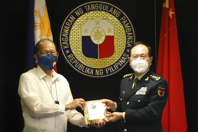 In this handout photo provided by the Department of National Defense Public Affairs Office (PAO), Philippine Defense Secretary Delfin N. Lorenzana, left, exchanges momento with his Chinese counterpart General Wei Fenghe during his visit at the Department of National Defense in Quezon city, Philippines, Friday Sept. 11, 2020. The two discussed ways in responding to the COVID-19 pandemic, revisited the 2004 Philippines-China Memorandum of Understanding (MOU) on Defense Cooperation and also issues on the South China Sea. (Department of National Defense PAO via AP)