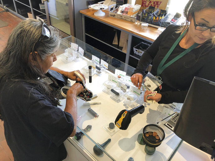 FILE - In this June 11, 2019, file photo, Minerva cannabis dispensary assistant manager Celina Roybal, right, sells a vial of marijuana to customer Tina Bernal, who uses cannabis to relieve chronic pain, in Santa Fe, N.M. New Mexico would use proceeds from recreational marijuana to eliminate taxes on medical cannabis and subsidize sales to low-income patients under a legalization proposal from an expert panel appointed by Gov. Michelle Lujan Grisham. The recommendations on Tuesday, Oct. 15, 2019, from a 23-member task force sets the stage for a new push to authorize the recreational use and sale of marijuana when the Legislature convenes in January 2020. (AP Photo/Morgan Lee, File)
