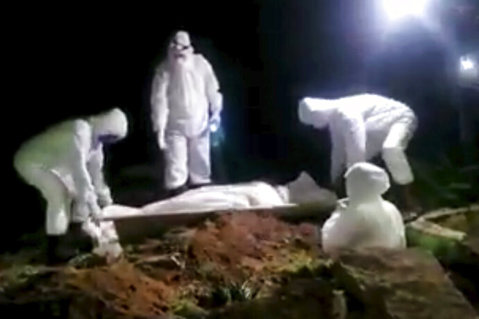 In this May 2020 frame grab from video provided by a Yemeni activist, men in protective gear bury a victim of COVID-19, in the Houthi-controlled city of Ibb, Yemen. An investigation by The Associated Press found that the coronavirus is taking a deadly toll on the war weary population of Yemen. The situation is exacerbated in the Houthi-controlled north where the rebels have suppressed information about the virus, severely punished those who speak out, enforced little mitigation measures, and promoted conspiracies and claims by the Houthi minister of health that scientists are working on developing a cure for covid-19 to present to the world. (Yemeni Activist via AP)