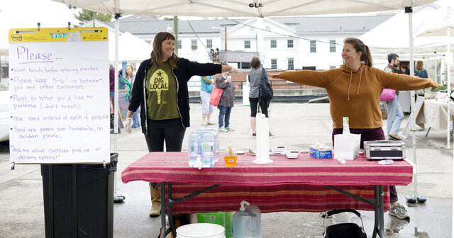 Katie Struble, mobile market manager, left, and Connie Kenny, market manager with Local Environmental Agriculture Project, Inc. (LEAP) farmers markets demonstrate social distancing as the Grandin Village Farmers Market was open with precautions on Saturday, March 21, 2020, in Roanoke, Va..