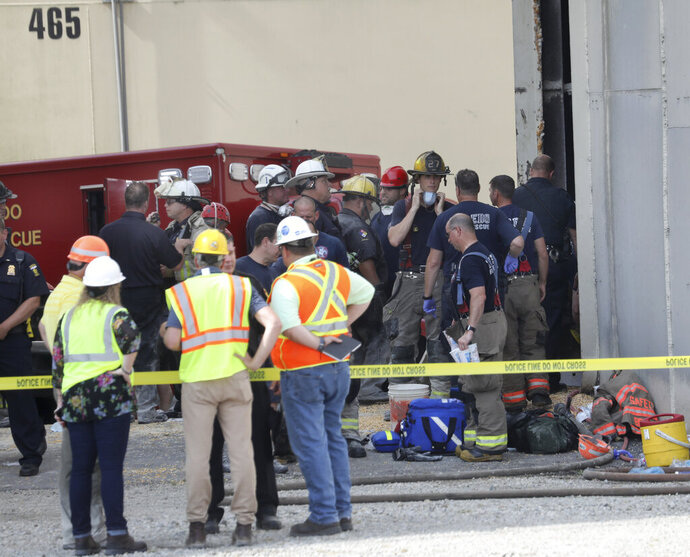 Toledo Fire and Rescue personnel stand outside an Andersons grain storage tank where two workers died after they were trapped in a silo filled with grain, Friday, July 19, 2019 in Toledo, Ohio.  The workers became trapped Friday morning inside the silo operated by The Andersons. (Dave Zapotosky /The Blade via AP)
