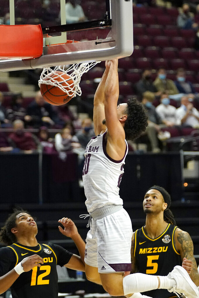 Texas A&M guard Andre Gordon (20) dunks the ball over Missouri guard Dru Smith (12) and forward Mitchell Smith (5) during the second half of an NCAA college basketball game Saturday, Jan. 16, 2021, in College Station, Texas. (AP Photo/Sam Craft)