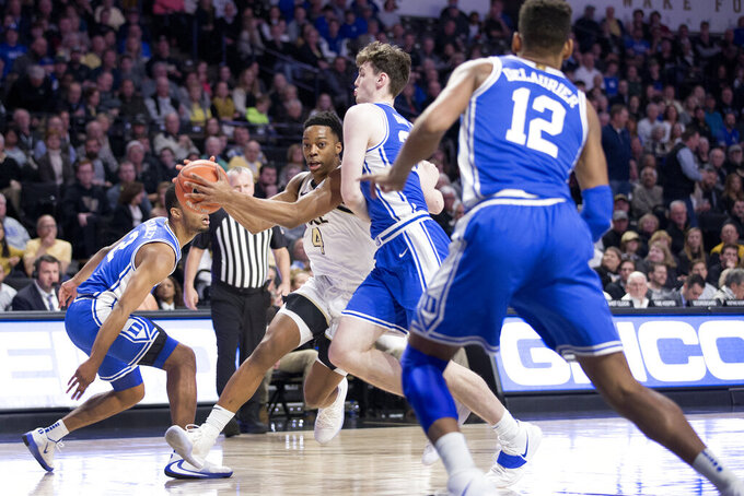 Wake Forest guard Jahcobi Neath (4) brings the ball down court between Duke defenders in the first half of an NCAA college basketball game Tuesday, Feb. 25, 2020, in Winston-Salem, N.C. (AP Photo/Lynn Hey)