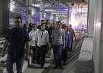"Indonesian President Joko ""Jokowi"" Widodo, center right, walks with Finance Minister Sri Mulyani, third left, and Jakarta Governor Anies Baswedan, left, in a Jakarta Mass Rapid Transit tunnel during the inauguration ceremony of the subway line in Jakarta, Indonesia, Sunday, March 24, 2019. The 16-kilometer (10-mile) line system running south from Jakarta's downtown is the first phase of a development that if fully realized will plant a cross-shaped network of stations on the teeming city of 30 million people. (AP Photo/Dita Alangkara, Pool)"
