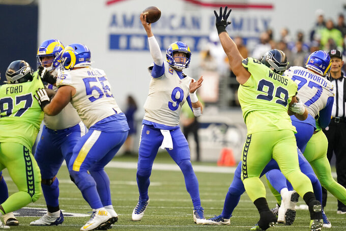 Los Angeles Rams quarterback Matthew Stafford (9) passes under pressure from Seattle Seahawks defensive tackle Al Woods (99) during the first half of an NFL football game, Thursday, Oct. 7, 2021, in Seattle. (AP Photo/Elaine Thompson)