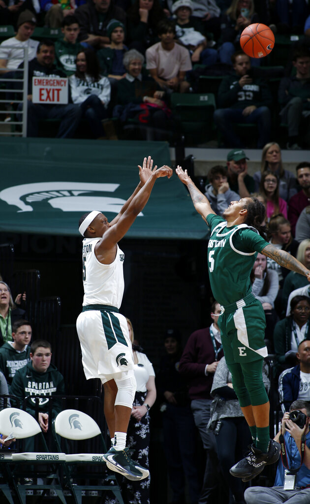 Michigan State's Cassius Winston, left, shoots a three-point basket against Eastern Michigan's Noah Morgan during the first half of an NCAA college basketball game, Saturday, Dec. 21, 2019, in East Lansing, Mich. (AP Photo/Al Goldis)