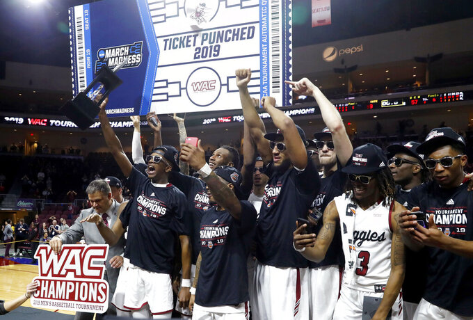 New Mexico State players and coaches celebrate with the trophy after the team's 89-57 win over Grand Canyon in an NCAA college basketball game for the Western Athletic Conference men's tournament championship Saturday, March 16, 2019, in Las Vegas. (AP Photo/Steve Marcus)