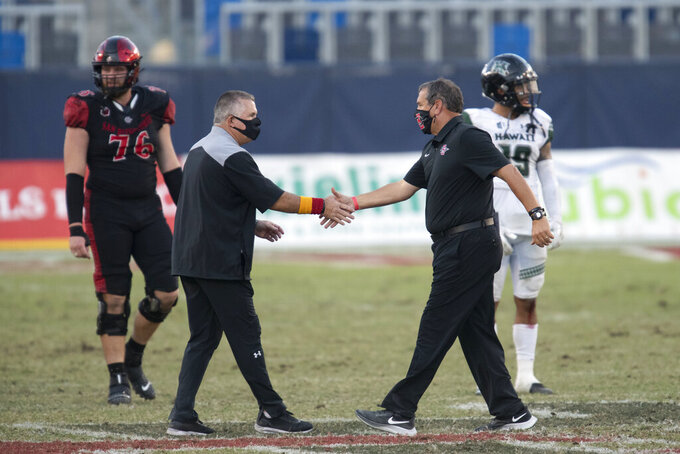Hawaii head coach Todd Graham, left, and San Diego State head coach Brady Hoke shake hands after an NCAA college football game Saturday, Nov. 14, 2020, in Carson, Calif.  (AP Photo/Kyusung Gong)