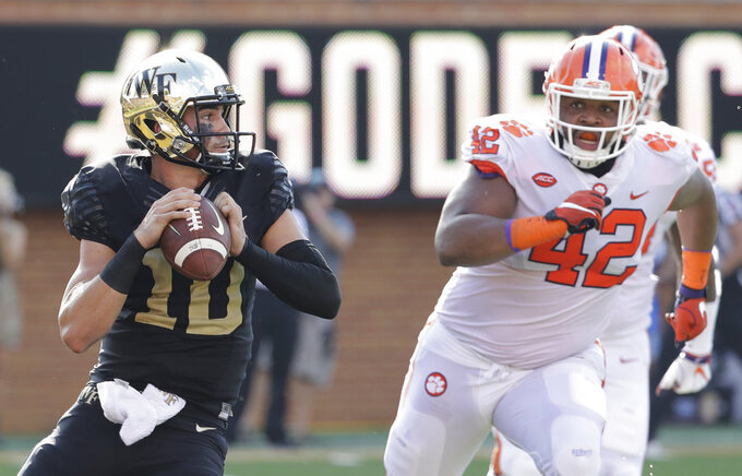 File-This Oct. 6, 2018, file photo shows Wake Forest's Sam Hartman (10) looking to pass under pressure from Clemson's Christian Wilkins (42) during the first half of an NCAA college football game in Charlotte, N.C. Wilkins is here to put a smile on your face, whether you like it or not. For four seasons, Wilkins has been bringing the jokes, zingers and sneaky pinches on the bottom at Clemson. The 300-pound All-America defensive tackle famously celebrated the Tigers' 2016 national championship with a split and flashed a Heisman pose after a touchdown run this season. (AP Photo/Chuck Burton, File)