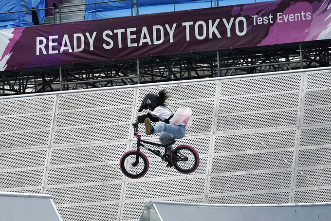 FILE - In this May 17, 2021, file photo, a local athlete competes during the Tokyo 2020 Olympic Game Cycling BMX Freestyle test event at Olympic BMX Course of Ariake Urban Sports Park in Tokyo. IOC officials say the Tokyo Olympics will open on July 23 and almost nothing now can stop the games from going forward. (AP Photo/Eugene Hoshiko, File)