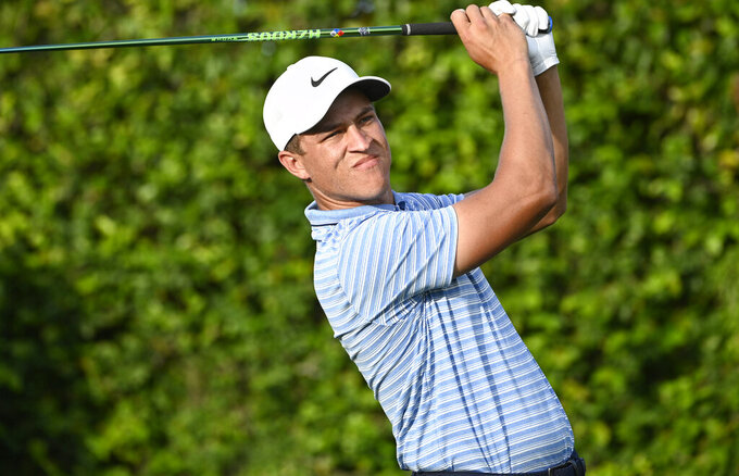FILE - In this March 5, 2020, file photo, Cameron Champ watches his tee shot on the ninth hole during the first round of the Arnold Palmer Invitational golf tournament in Orlando, Fla. Champ tested positive for the coronavirus on June 23 but was allowed to return this week at the Rocket Mortgage Classic under an adjusted policy for players who test positive with no symptoms who then test negative twice 24 hours apart. (AP Photo/Phelan M. Ebenhack, File)