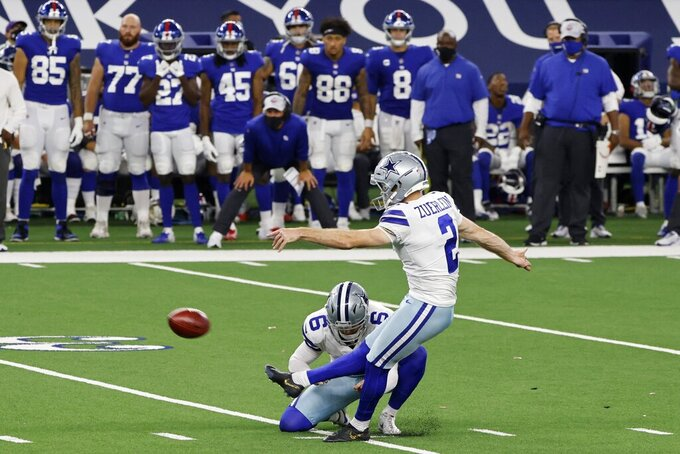 Dallas Cowboys punter Chris Jones (6) holds for place kicker Greg Zuerlein (2) who kicks a field goal as the New York Giants bench looks on late in the second half of an NFL football game in Arlington, Texas, Sunday, Oct. 11, 2020. (AP Photo/Ron Jenkins)