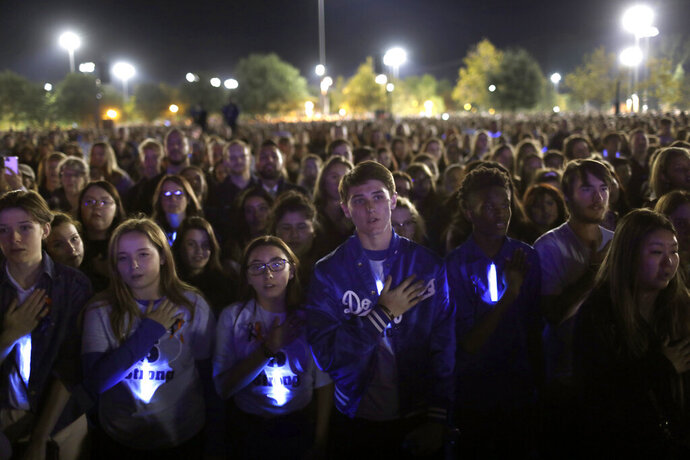 Students say the Pledge of Allegiance as thousands gather at a candlelight vigil for several students killed in the Saugus High School shooting in Central Park, Sunday, Nov. 17, 2019, in Santa Clarita, Calif. Detectives were searching for a motive for the killings carried out by Nathaniel Tennosuke Berhow on Thursday, his 16th birthday. (Carolyn Cole/Los Angeles Times via AP)